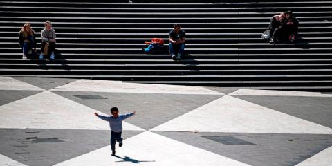 A boy runs across a square in Stockholm, Sweden on May 8, 2020.