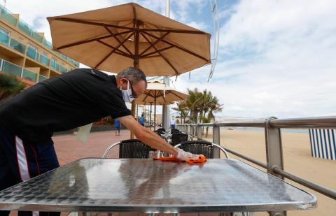 Un camarero desinfecta una mesa en la playa de Las Canteras de Gran Canaria