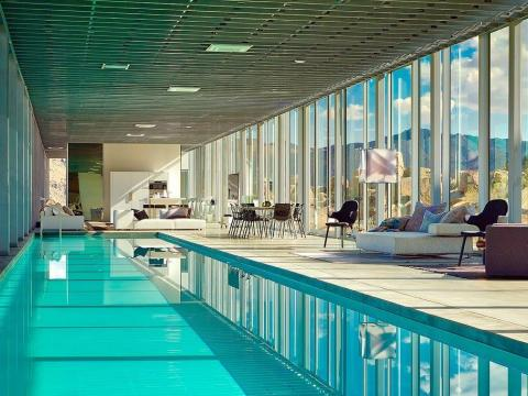 The central living space includes a 100-foot-long pool and mix of seating areas.