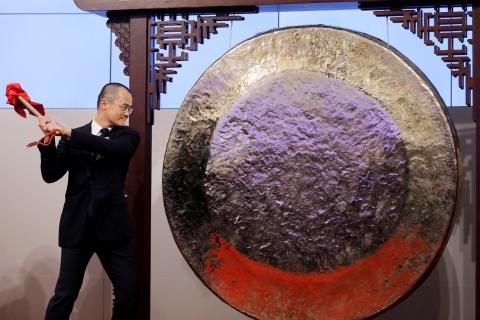 El CEO de Meituan Dianping, Xing Wang, golpea un gong en el debut de su empresa en el índice hongkonés.
