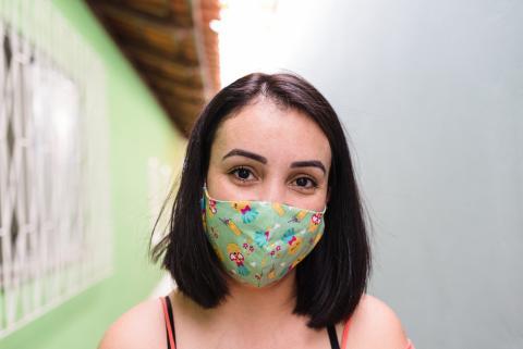Una chica joven utiliza una mascarilla de tela para protegerse del coronavirus
