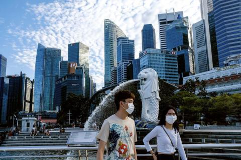 Una pareja con mascarillas camina por Singapur durante el brote de coronavirus del 14 de marzo de 2020.