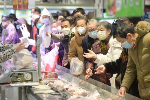 Clientes con mascarillas realizan sus compras dentro de un supermercado tras un brote del coronavirus en Wuhan, provincia de Hubei, China, el 10 de febrero de 2020.
