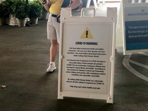 Señal de advertencia de Disney Springs sobre el COVID-19.