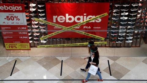 Dos mujeres con mascarilla y pantalla pasean por un centro comercial de Madrid