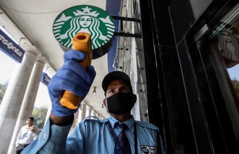 Un empleado controla la temperatura en la puerta de un Starbucks