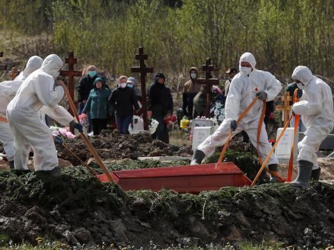 Excavadores de tumbas bajan el ataúd de una persona que supuestamente murió de un coronavirus, mientras los enlutados con máscaras se reúnen en un cementerio en las afueras de San Petersburgo, Rusia, el 13 de mayo de 2020.