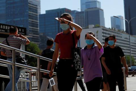 Un grupo de personas camina por la calle en Pekín en medio del segundo brote de coronavirus en China