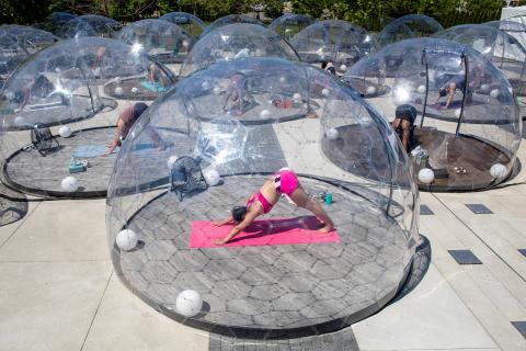 Un grupo de personas participa en una clase al aire libre en Toronto (Canadá) dentro de cúpulas para garantizar el distanciamiento social.