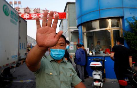 Un guardia de seguridad intenta bloquear una cámara fuera del mercado de mariscos Jingshen, cerrado tras detectar nuevas infecciones por coronavirus, en Beijing, China.
