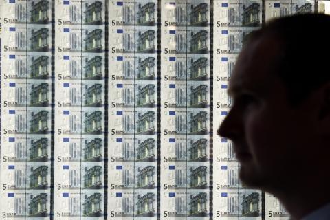 Un hombre delante de una plancha de billetes de euro