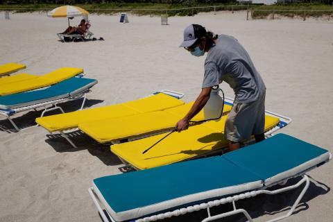Un hombre desinfecta unas hamacas en Florida, EEUU.