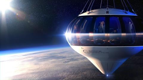 An illustration of Space Perspective's planned crew capsule, the Neptune, dangling from the end of a stratospheric balloon with eight passengers and a pilot inside. Space Perspective