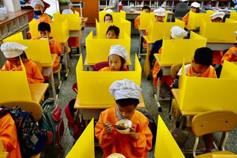 Students eat their lunch on desks with plastic partitions as a preventive measure to curb the spread of the COVID-19 coronavirus at Dajia Elementary School in Taipei on April 29, 2020.