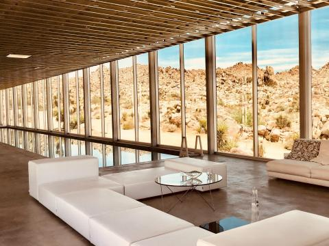 The interior of the home is minimalistic with floor-to-ceiling windows.