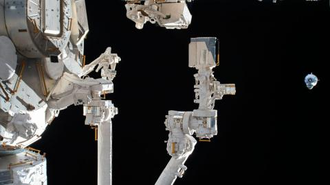 El SpaceX Crew Dragon (derecha) se acerca a la Estación Espacial Internacional. En primer plano está el brazo robótico conectado al módulo de laboratorio Kibo de la Agencia de Exploración Aeroespacial de Japón.