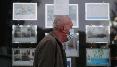 Un jubilado con mascarilla pasa ante una inmobiliaria en Madrid