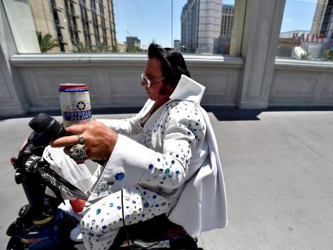 Un imitador de Elvis conduce su motocicleta por un puente peatonal en Las Vegas el 4 de junio de 2020.