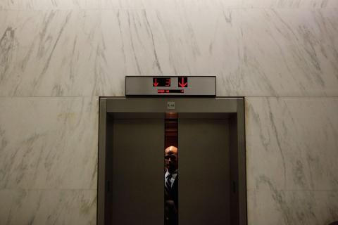 A man riding an office elevator.