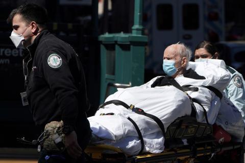 Llevan a un paciente en camilla a una ambulancia en Nueva York el 27 de marzo.