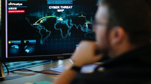 Un analista de ciberseguridad comprueba un mapa con ciberamenazas.