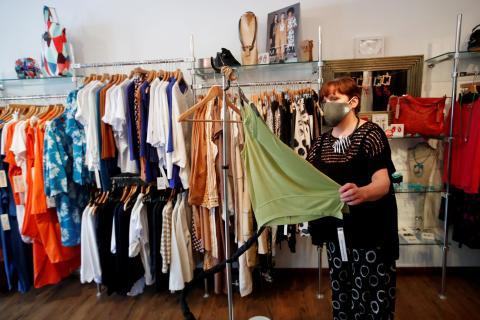 Una mujer limpia la ropa de su tienda con vapor durante el coronavirus.