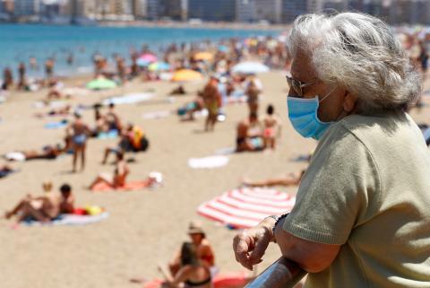 Una mujer con una mascarilla contempla las vistas en la playa de Las Canteras, en Las Palmas de Gran Canaria, el pasado 31 de mayo