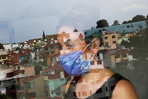 Una mujer con mascarilla mira por la ventana durante la crisis del coronavirus en México.