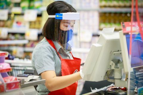 Mujer con pantalla de protección facial en un supermercado