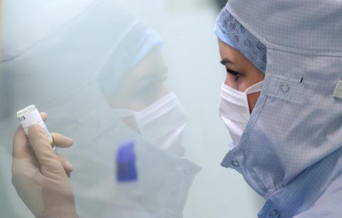 Una mujer prepara la medicación para enfermos de COVID-19 en un hospital.