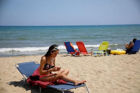 Una mujer utilizando su móvil en la playa, en Italia.