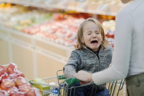 Niña en el supermercado llorando en el carrito.