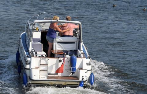 Una pareja conduce su crucero a motor a lo largo del río Támesis en el oeste de Londres, Gran Bretaña.