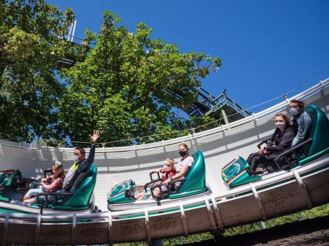 Adultos y niños con mascarillas en la atracción de un parque recién reabierto.