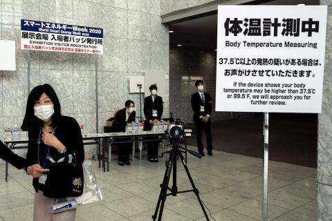 Personas con mascarillas cerca de una máquina que mide la temperatura corporal en un salón de convenciones en Tokio, Japón, el 27 de febrero de 2020.