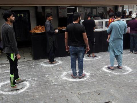 Las personas se paran en las marcas manteniendo una distancia segura, mientras compran comida para romper el ayuno, ya que el mes de ayuno musulmán del Ramadán comienza en Lahore, Pakistán, el 25 de abril de 2020.