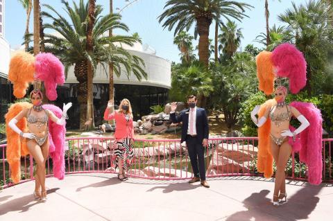 La presidenta regional de Caesars Entertainment, Eileen Moore, y el director general de Flamingo Las Vegas, Ken Janssen, posan con las bailarinas en la reapertura del Flamingo Las Vegas el 4 de junio de 2020.