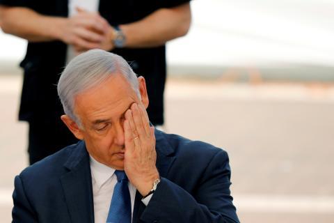 El Primer Ministro israelí Benjamín Netanyahu se toca la cara durante la ceremonia de apertura del curso escolar en el asentamiento judío de Elkana, en la Ribera Occidental ocupada por Israel.