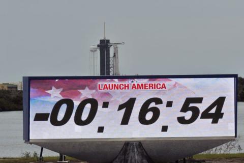 Pantalla que muestra el reloj de cuenta regresiva con el cohete SpaceX Falcon 9 y la nave espacial Crew Dragon en el fondo mientras se posponía el lanzamiento del Centro Espacial Kennedy de la NASA, en Cabo Cañaveral, Florida, EE. UU., 27 de mayo de 2020.
