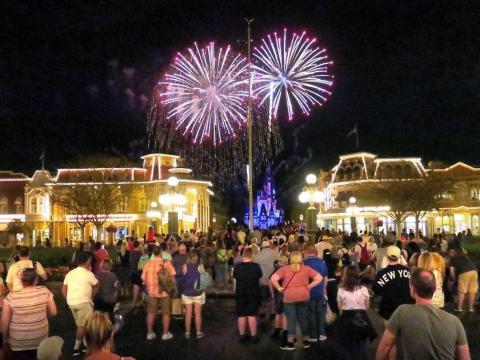 Gente viendo fuegos artificiales en Walt Disney World Orlando antes de que el parque cerrara el 15 de marzo.