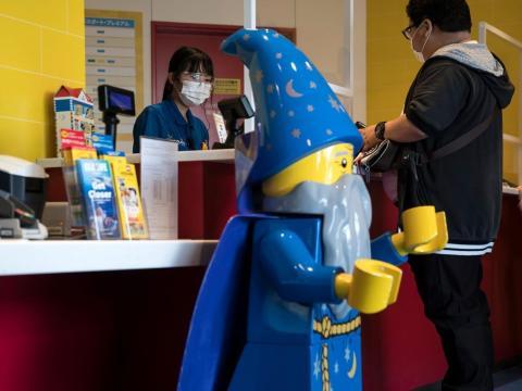 Una empleada detrás de láminas de plástico en la taquilla de Legoland.