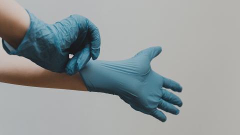 Tocar el exterior de guantes desechables contaminados.