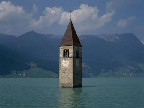 The Tower of Curon sticks out of Lake Resia, Italy, the only remnant of the town.