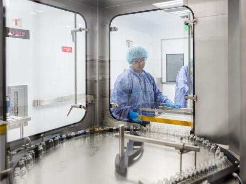 Un trabajador lava viales vacíos de remdesivir en una planta de Gilead