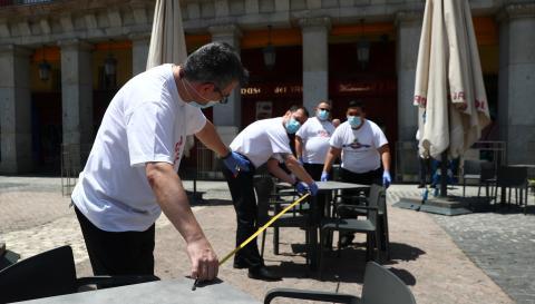 Trabajadores de un bar de la Plaza Mayor de Madrid miden la distancia entre mesas al reabrir tras el coronavirus