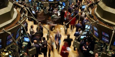 Traders working on the floor of the New York Stock Exchange are blur in this time exposure, just before the opening bell, 11 May, 2004.