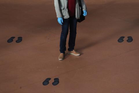 Un viajero con guantes protectores se para en medio de las marcas de distanciamiento social en el piso de la estación de trenes de Atocha.
