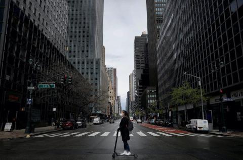 Una mujer con mascarilla conduce un scooter por una casi vacía 3ª Avenida en el centro de Manhattan, Nueva York, el 21 de abril de 2020.