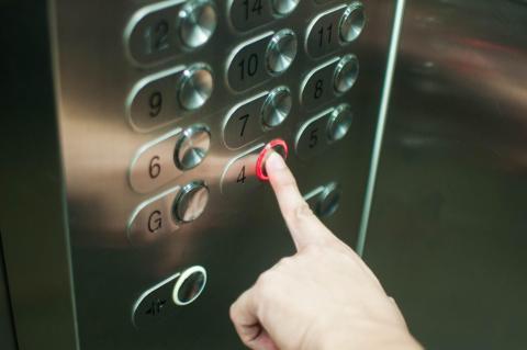 A women presses an elevator button.