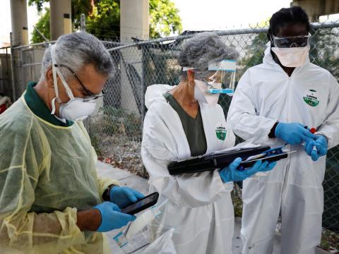 Trabajadores recogen muestras de personas sin hogar durante una acción de pruebas de coronavirus en el condado de Miami-Dade, en Florida, el 16 de abril de 2020.